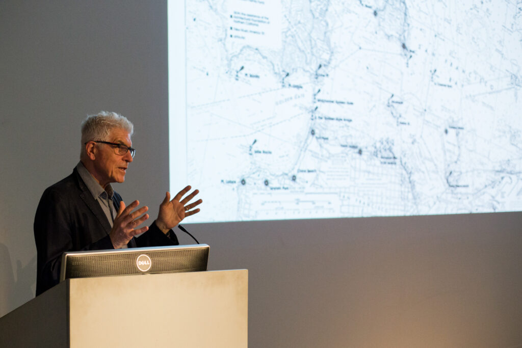 Bill Fontana gesturing with his hands while giving his lecture.