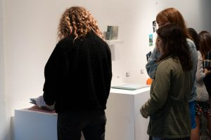 Person wearing gloves and reading a book at the DMA senior show.