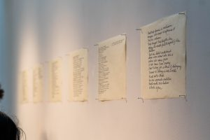 Handwritten art pinned to the gallery wall at the DMA senior show.