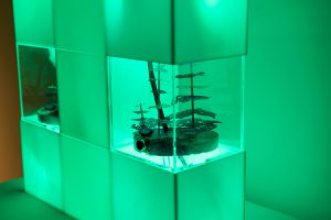 Model of a growing ecosystem inside an acrylic housing. Green leds surround the acrylic housing.