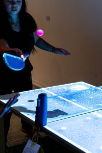 Person playing ping pong on a ping pong table with an overhead projection.