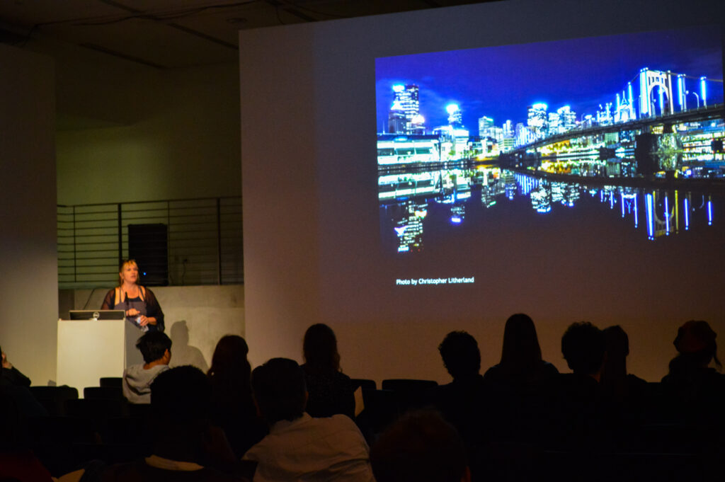 Photo of a city at night by Christopher Litherland is projected on the EDA pit wall.