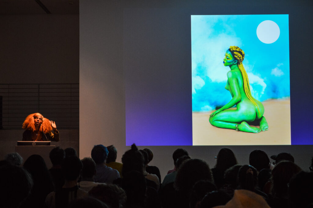 JULIANA HUXTABLE is standing next to a painting being projected in the EDA pit.