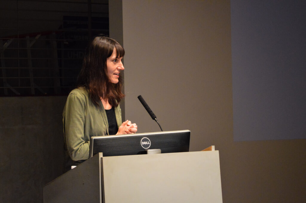 Astra taylor is speaking at a pedestal.