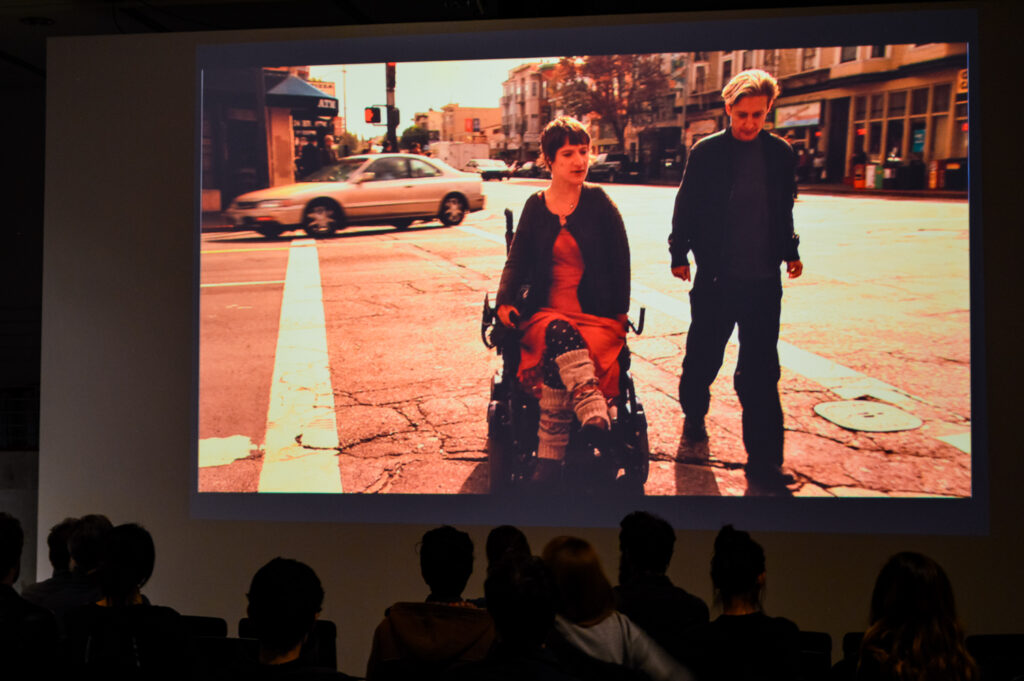 Movie still of a person in a wheel chair accompanied by a person walking beside the wheelchair person on the right.