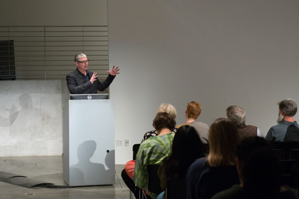Peter Lunenfeld is introducing Helen Molesworth, the guest lecturer, to the the pedestal.
