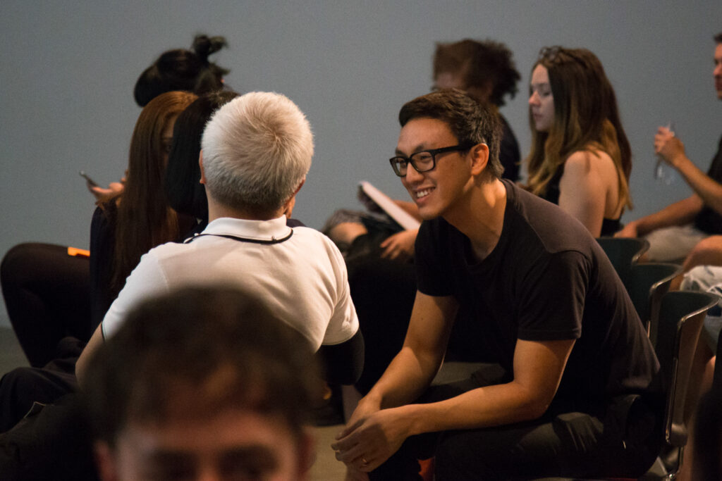 Ian Cheng smiling and talking to an audience member.