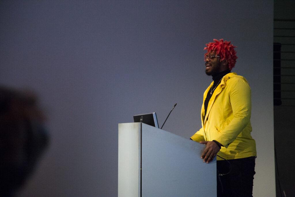 Ka5sh at the EDA pit podium wearing a yellow jacket.