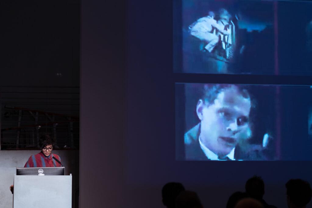 Screengrab of a man kissing someone in cinema.