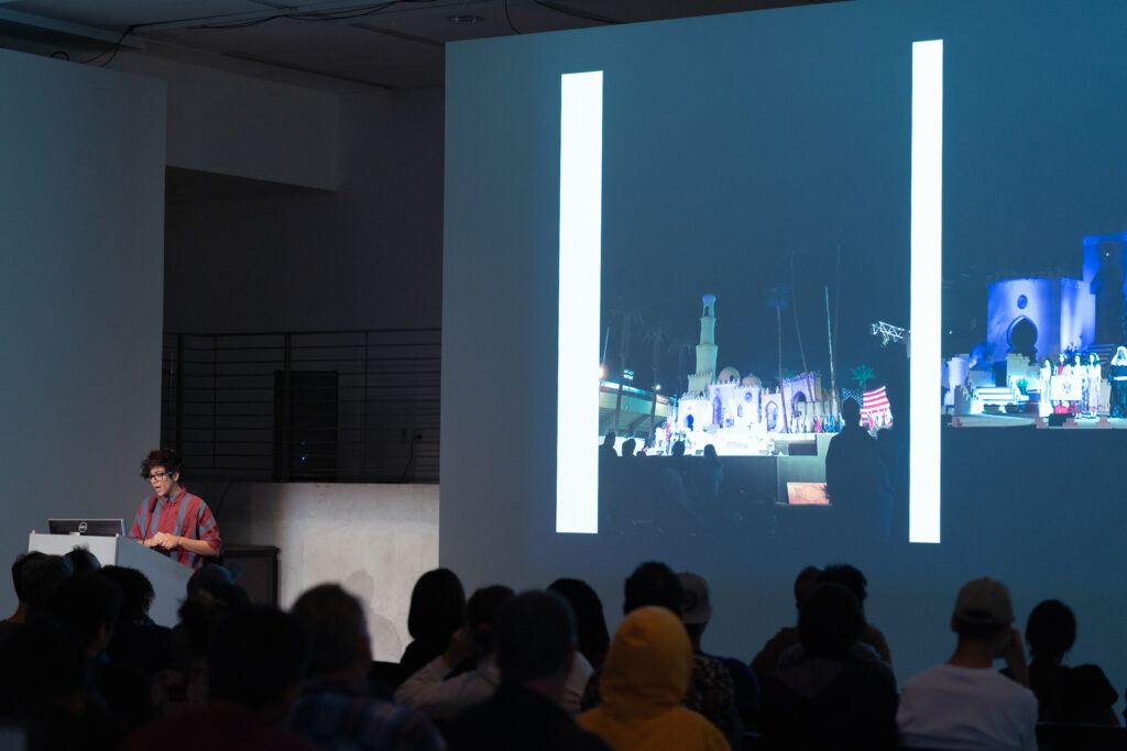 Gelare Khoshgoran is standing at a pedestal talking to the EDA pit audience.