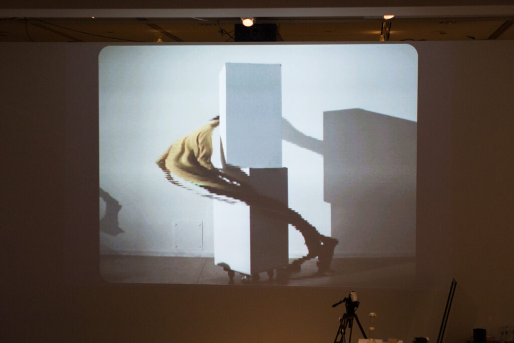 Live slit screening video manipulation of Toshio Iwai in front of a wall.
