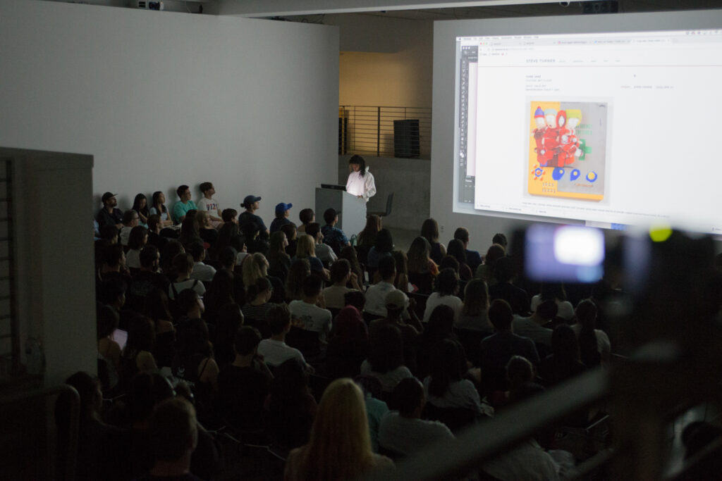 Yung Jake showing his paintings on the internet during his lecture.