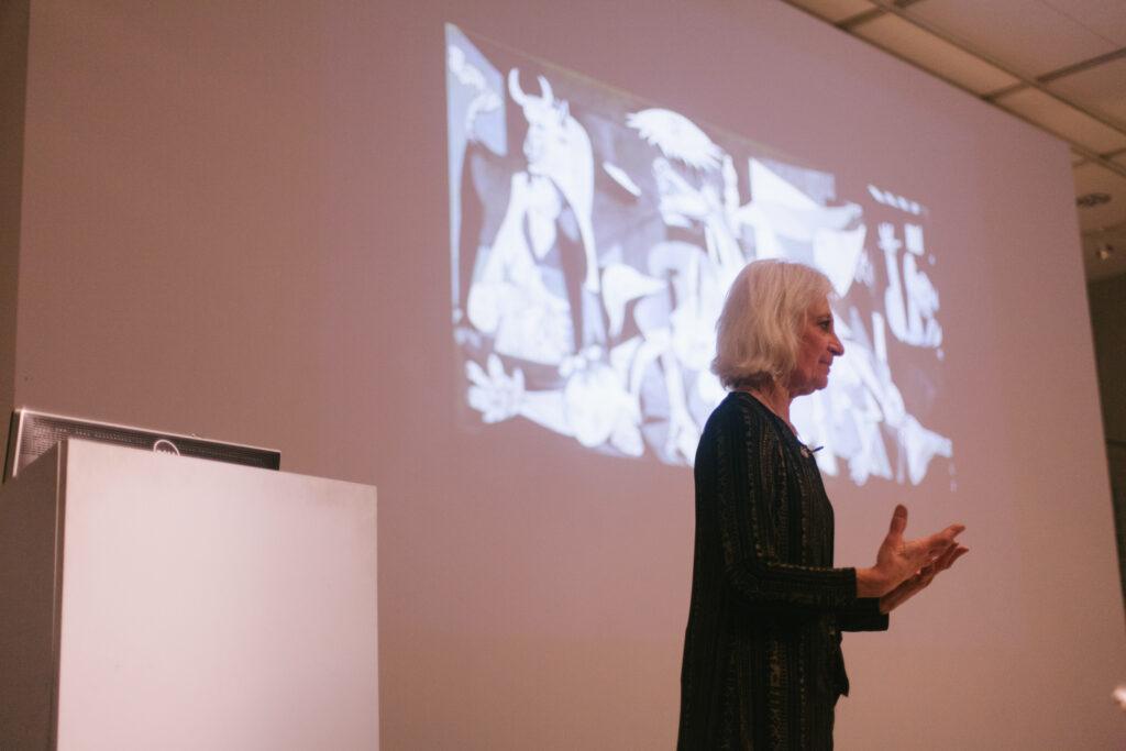Linda Weintraub is gesturing in front of her power point slide.