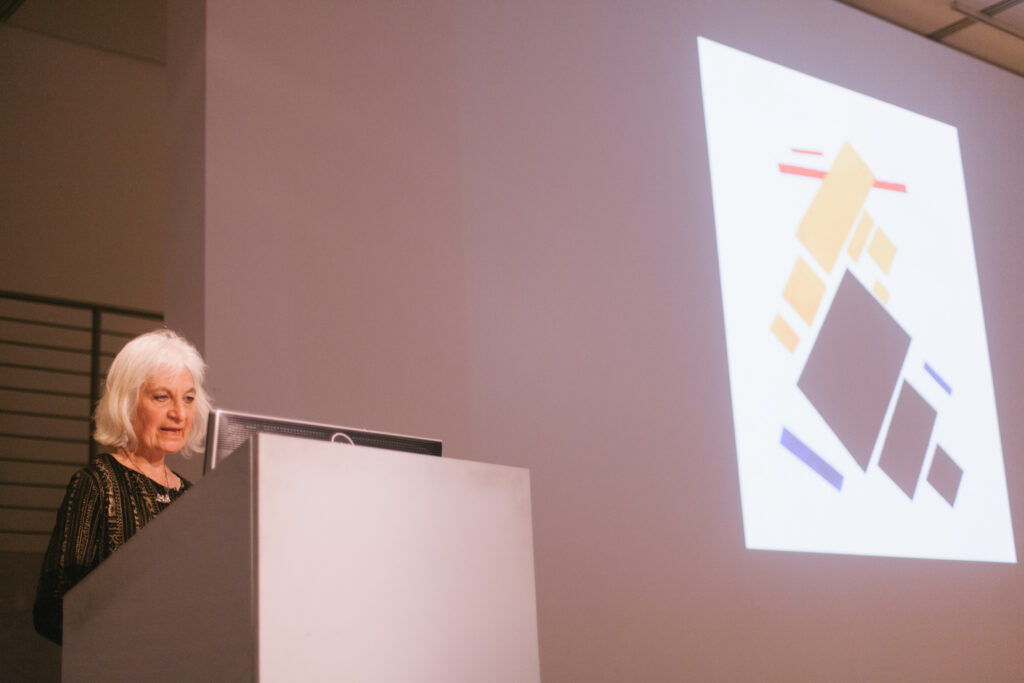 Lina Weintraub's lecture presentation. Lina is showing graphics of red, black, and blue rectangles being projected on the EDA walls.