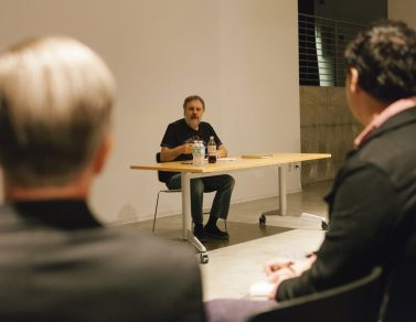 Slavoj Zizek talking to the crowd while sitting at a table.