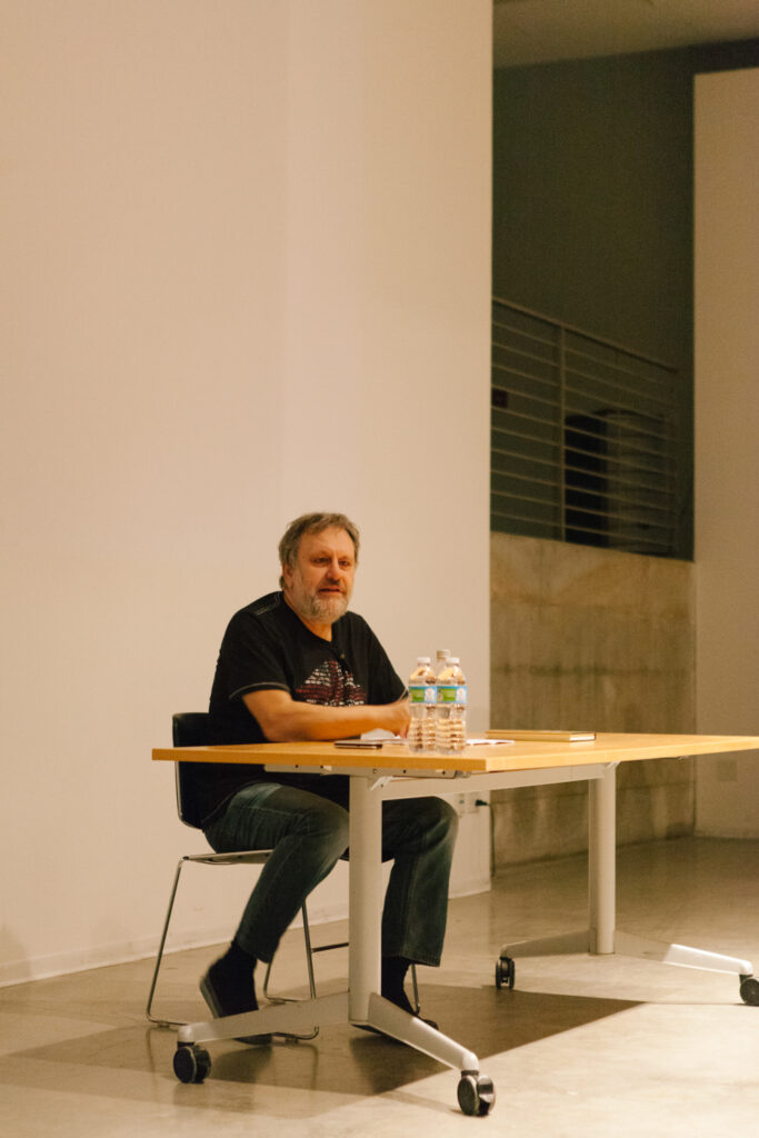 Zizek is sitting at a desk talking to an audience.