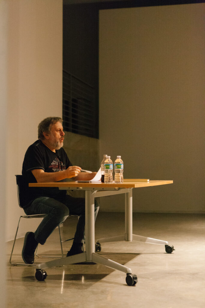 Zizek is sitting at a desk holding a pen and paper.