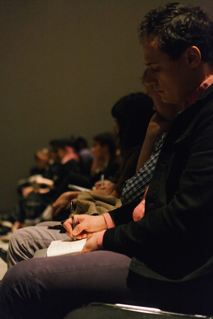 Person taking notes at Zizek's lecture.