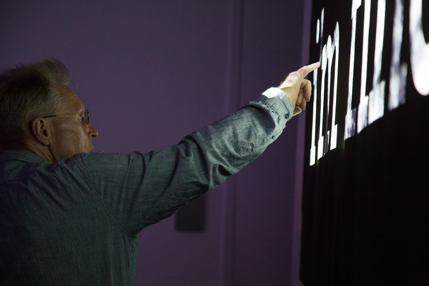 Carlos Garcia's solo show. Person pointing to text being projected within a typeface.