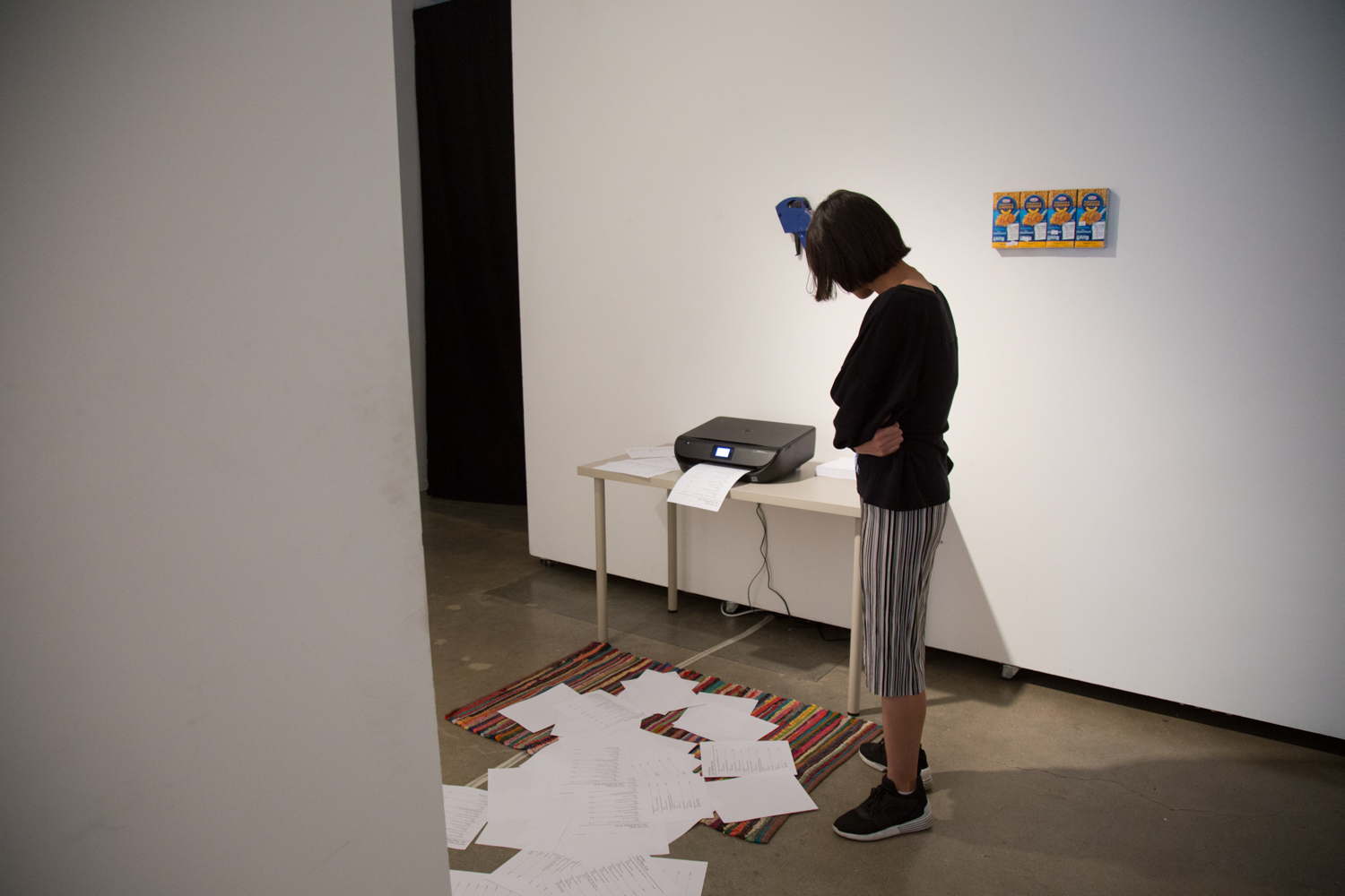 Person looking at a printer, printing a pile of papers onto the floor.