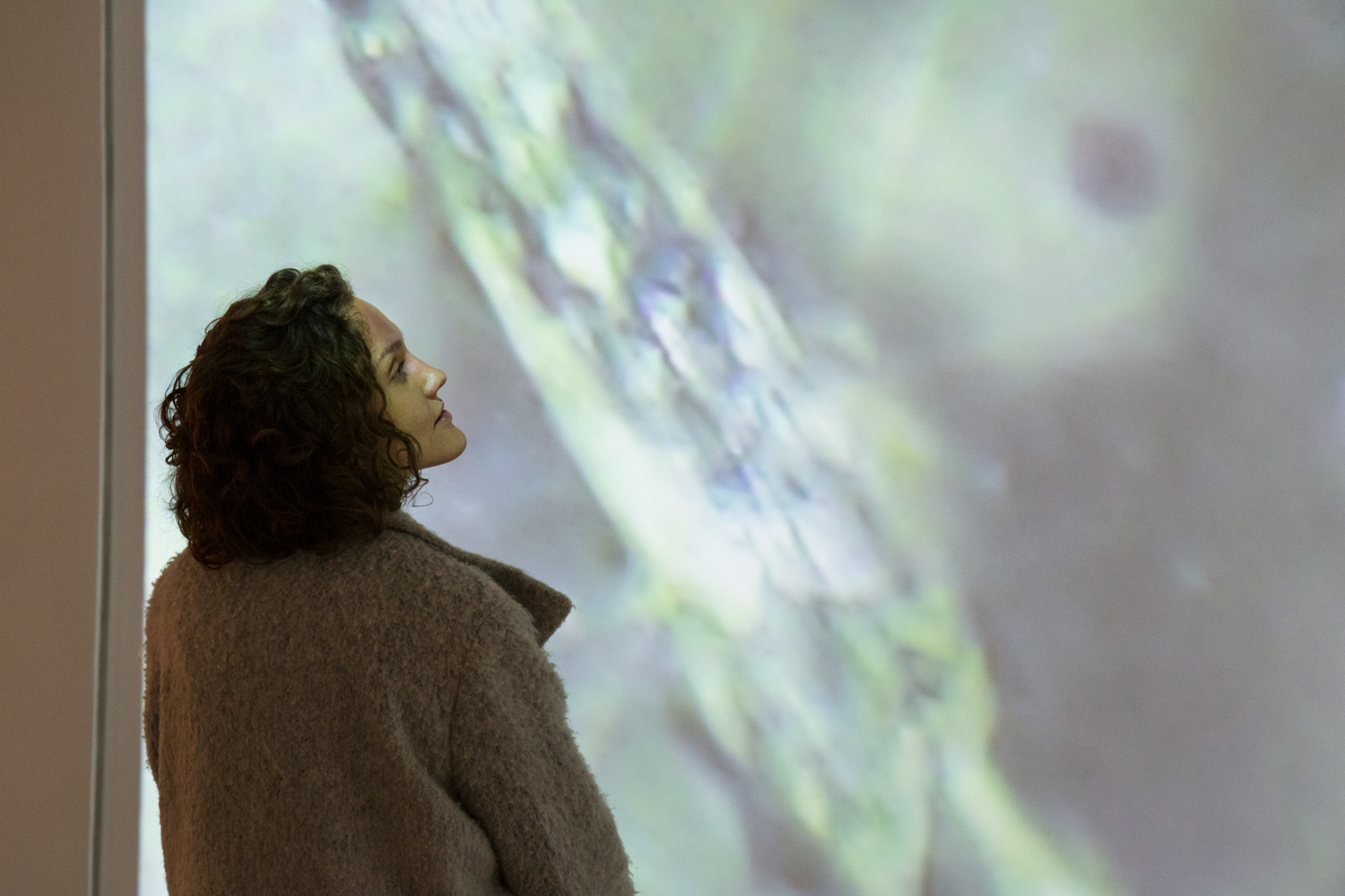Person looking up at a projection during Maru Garcia's solo show.