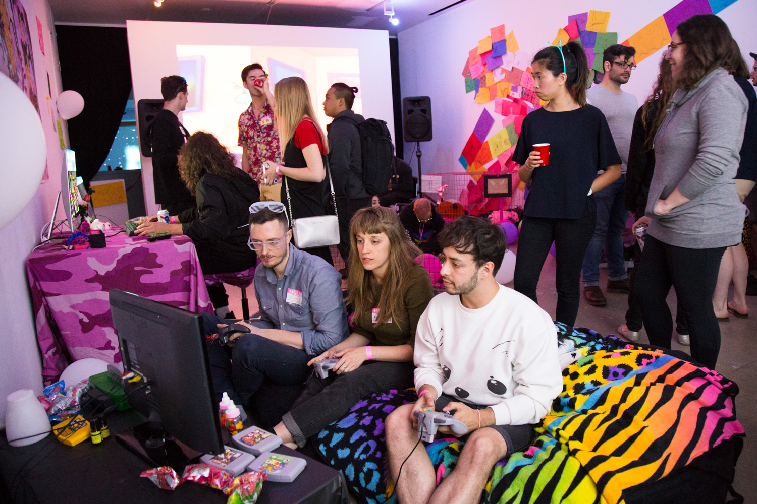 People crowded around a tv monitor, playing a game. The tv monitor is on the floor and the people are sat on a zebra print throw blanket.