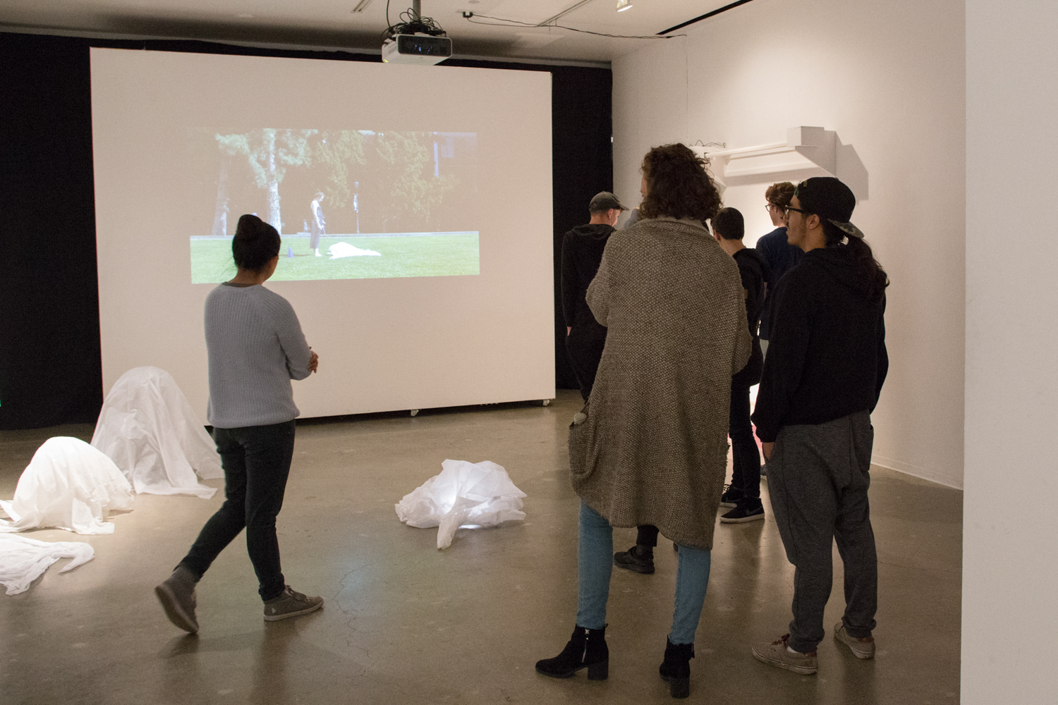 Video work of a person standing in a garden at Sam Congdon's solo show.