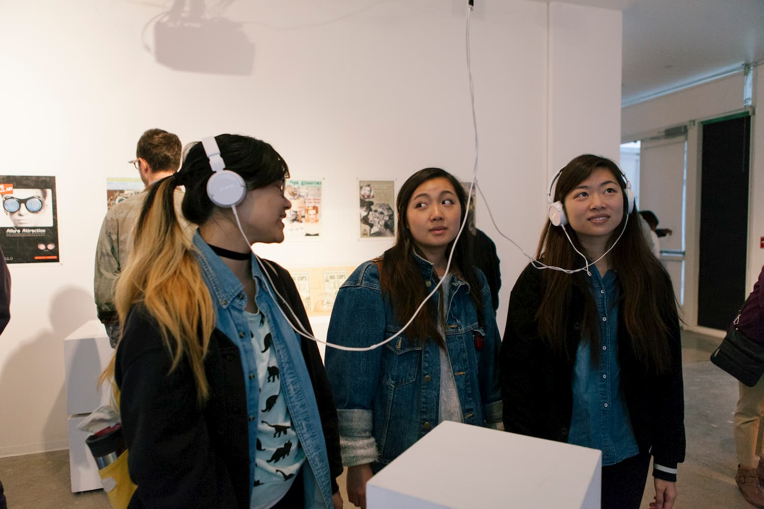 People wearing headphones looking up at a monitor pictured out of frame.