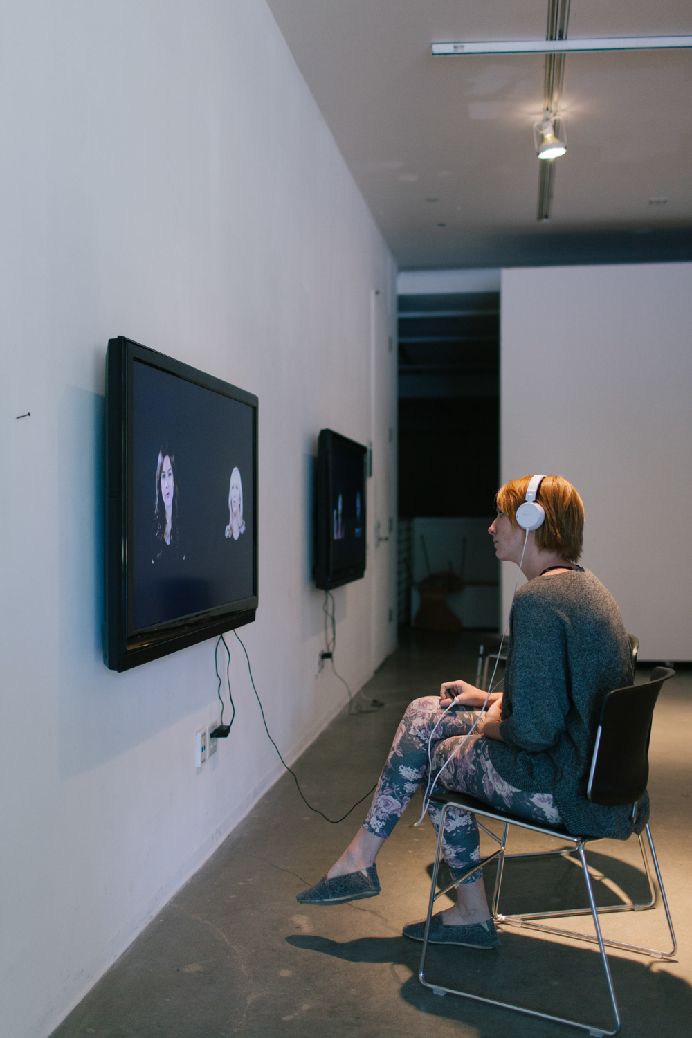 Person with headphones sitting in front of Iglesias' solo show work.