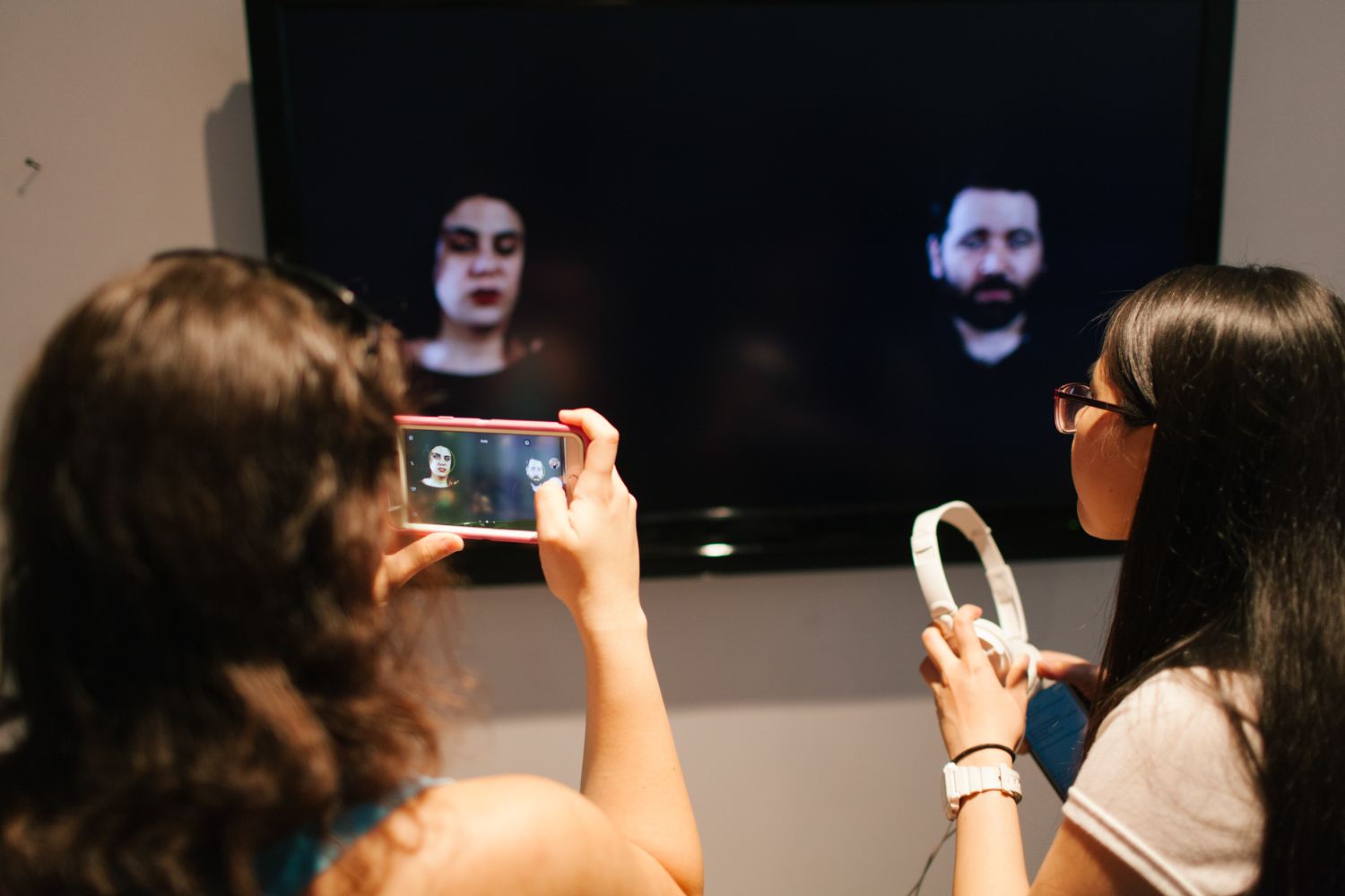 Person taking a photo of two people being displayed on a tv monitor.