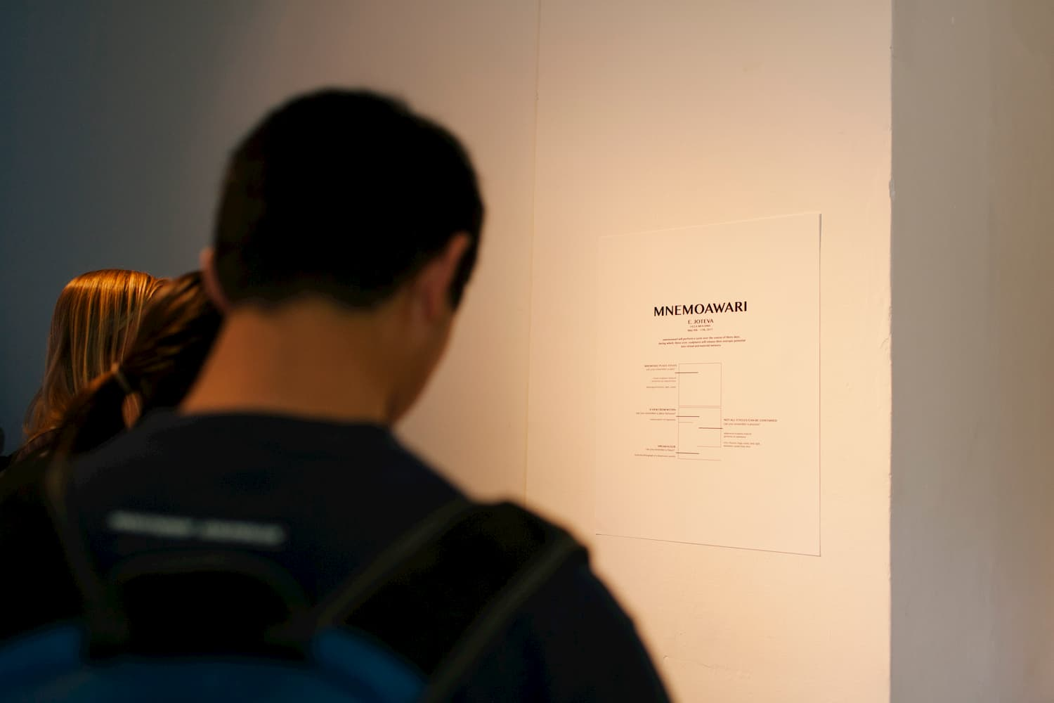 Person looking at the press release for Joteva's solo show MNEMOAWARI.