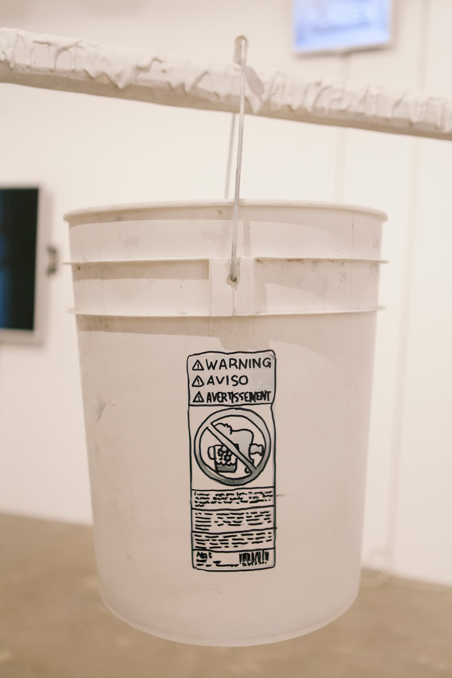 A white painter bucket hung on a frame during Stalgia Grigg's solo show.