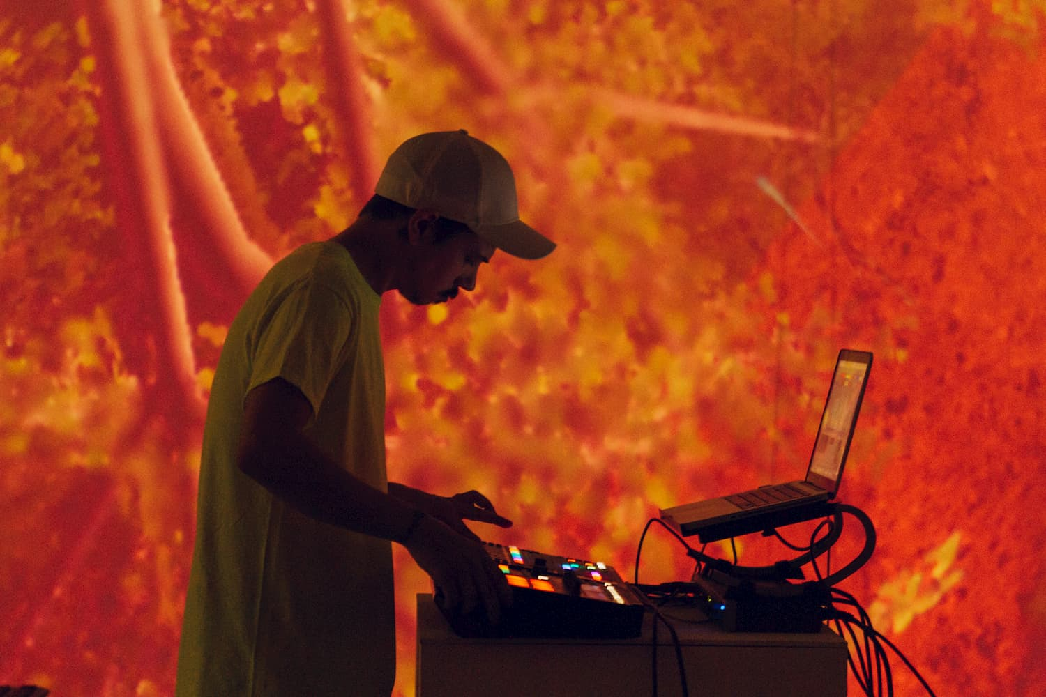 Person mixing audio in front of red hue projection visual.
