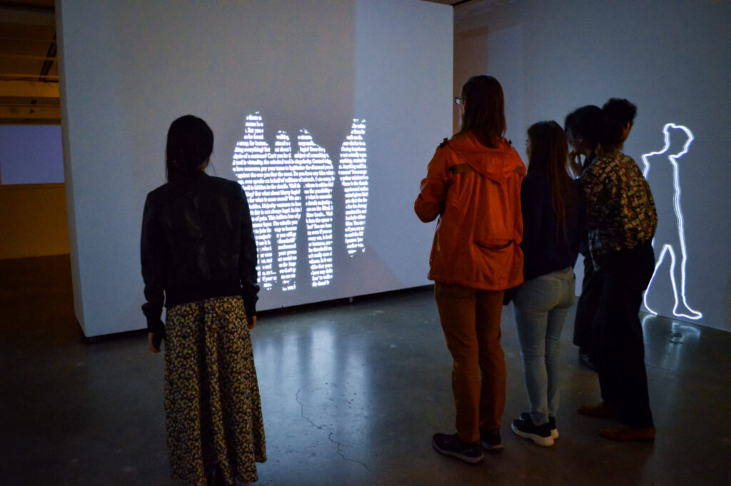 ZEYNEP ABES projection of people on a wall. There is text within the people being projected.