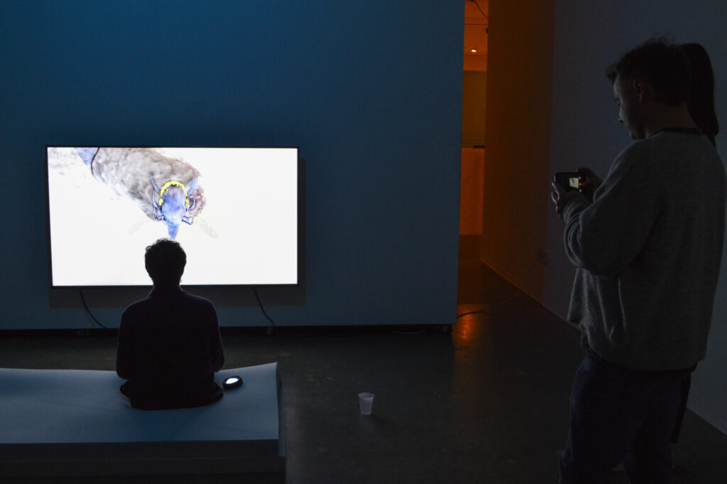 MILES PEYTON Solo Exhibition – GROOM. Person sitting on a mattress playing a video game.