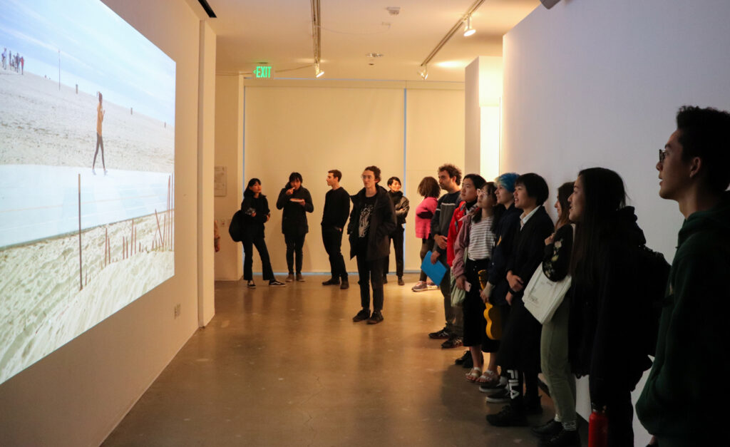 People look at Harvey Moon's projection work during Harvey Moon's exhibition opening.