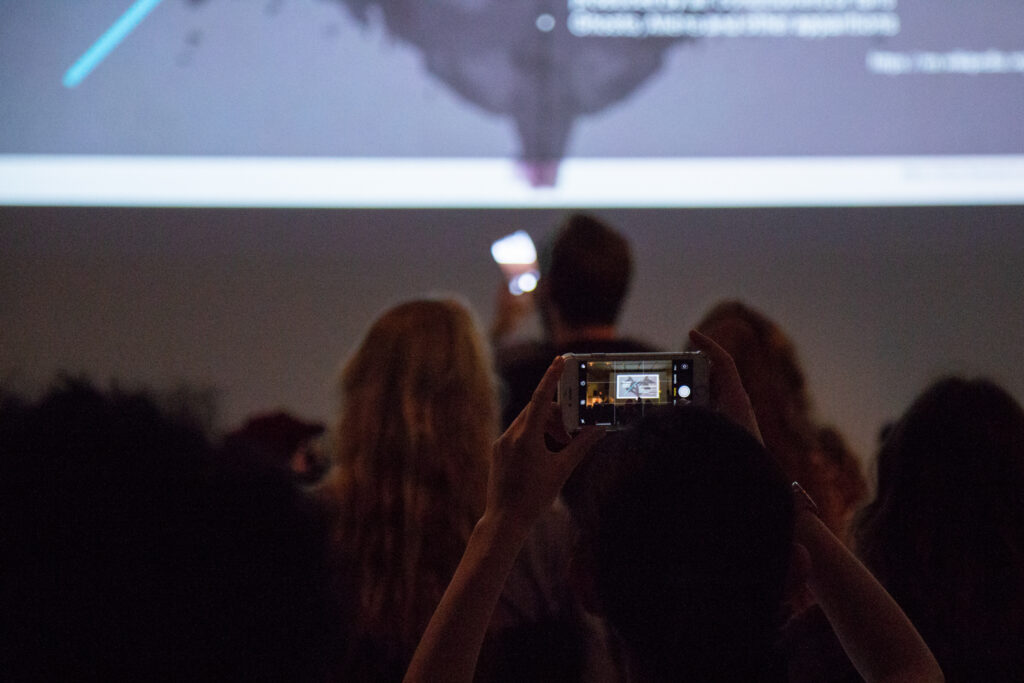 Audience member taking a picture of a projected slide with their phone.