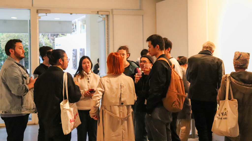 People socializing at the opening of Zheng Fang's exhibition.