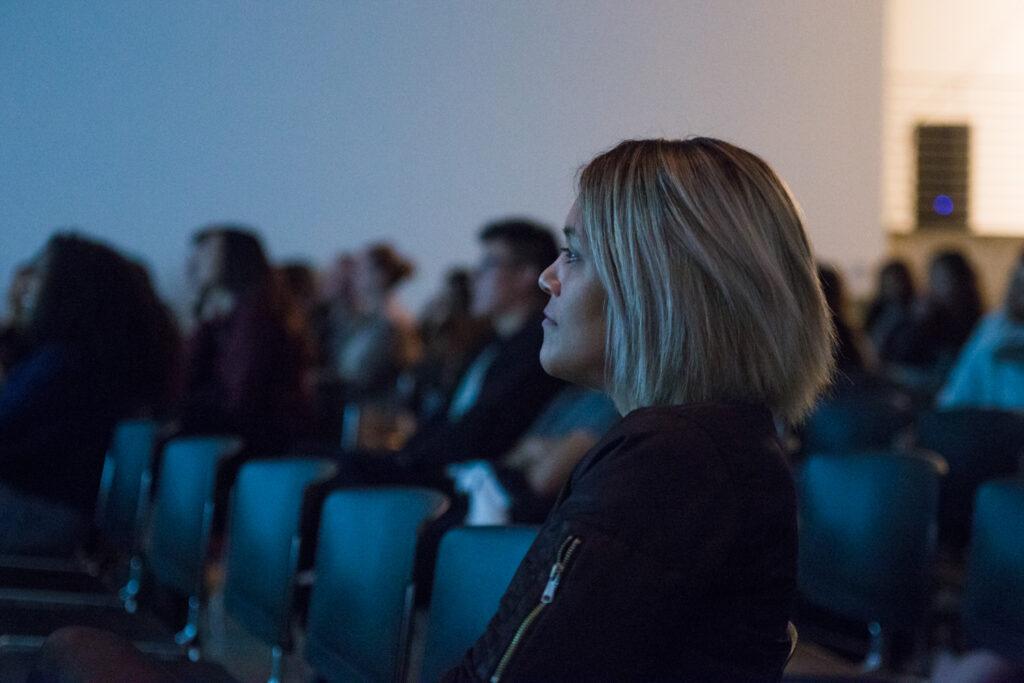 Audience member looking at the work of Angela Washko.