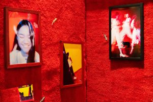 Red carpet wall with mounted photographs of a woman dancing.