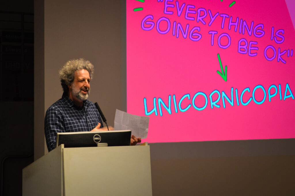 Edo Stern talks at a pedestal next to a slide that is projected displaying the word, Unicornicopia.