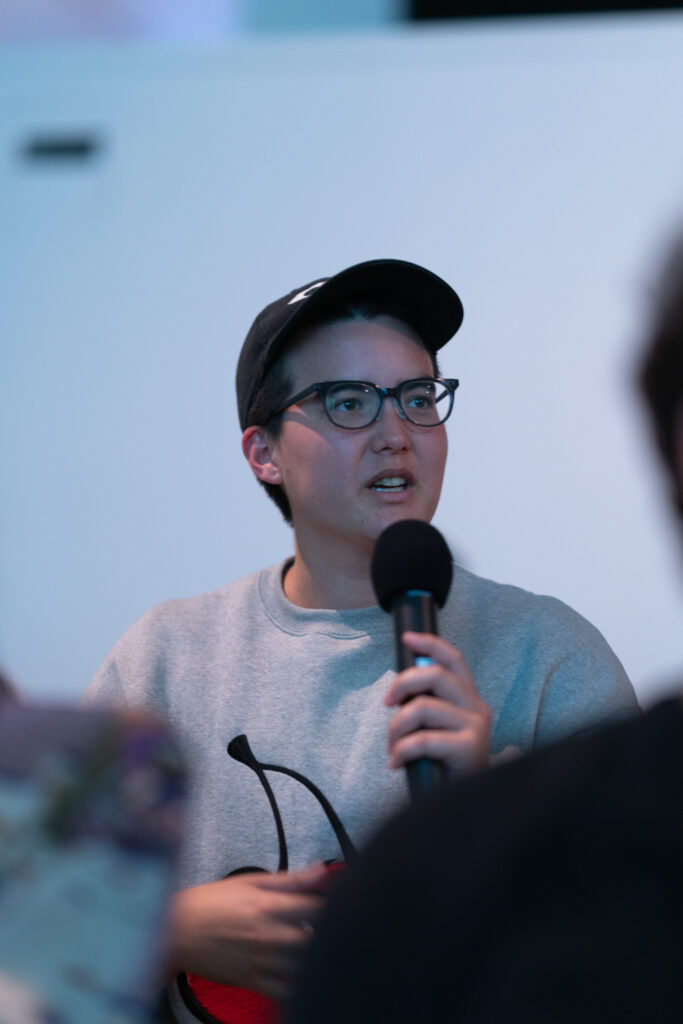 Person wearing a cap is talking into a microphone.