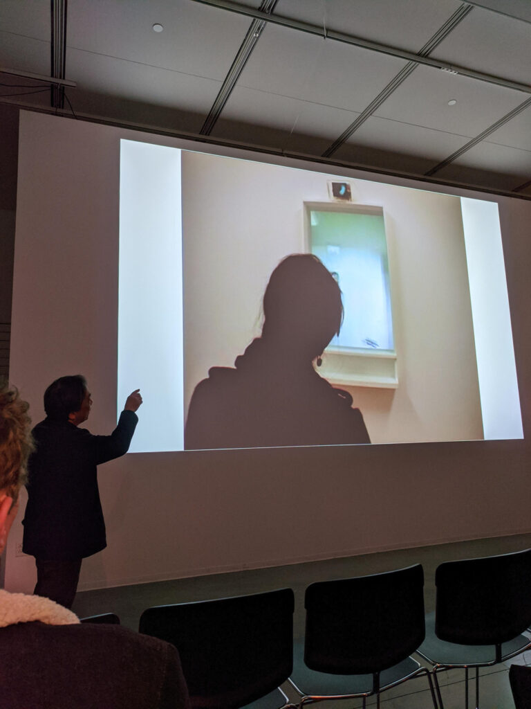 MASAKI FUJIHATA points to documentation of his work being projected on the walls of the EDA pit. The documentation is a person standing in front of a window.