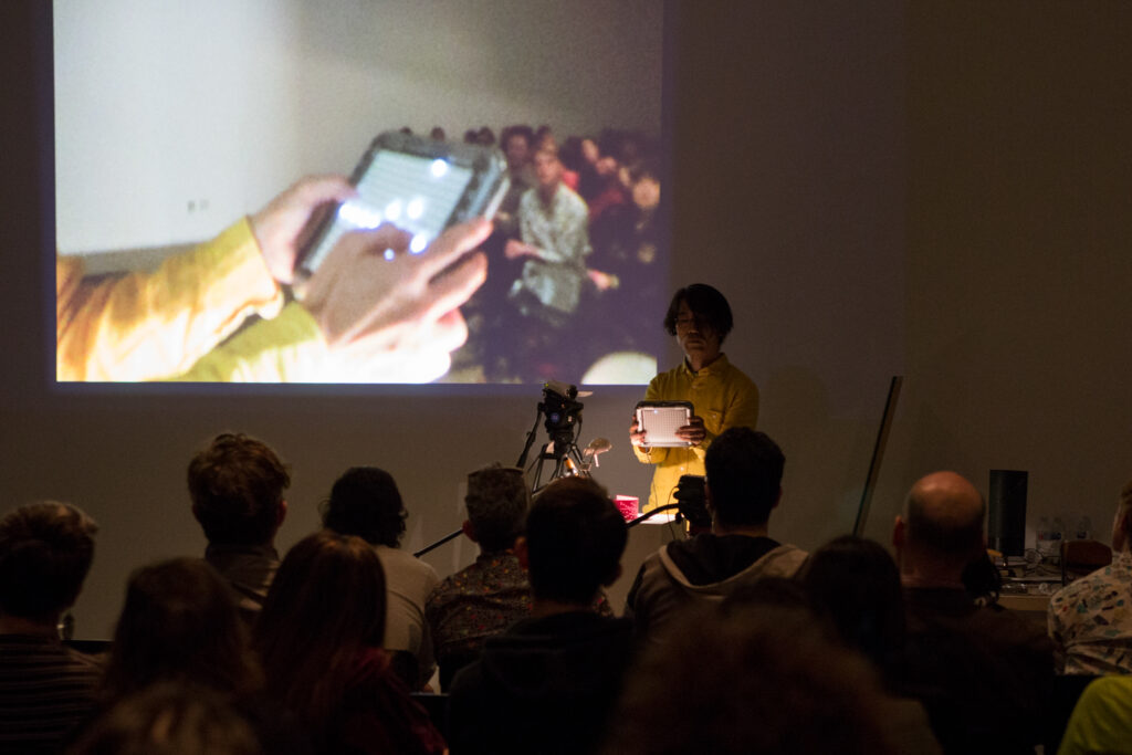 Toshio Iwai is holding some sort of handheld LED lit controller.
