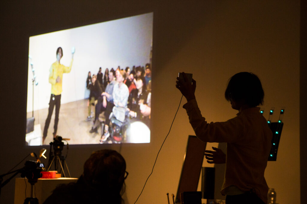 Toshio Iwai holding a camera that is capturing a live feed of the audience standing in front of Toshio.