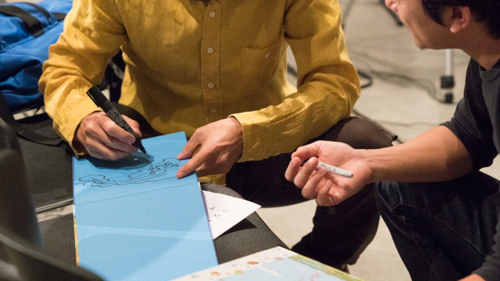 Toshio Iwai is drawing a picture on blue paper.