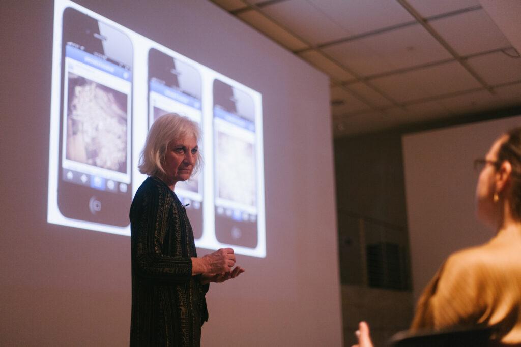 Linda Weintraub is standing in front of her power point slide displaying phones.