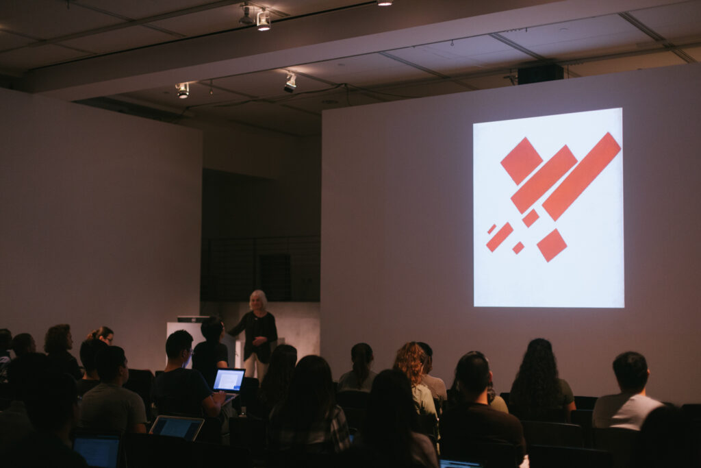 Lina Weintraub's lecture presentation. Lina is showing graphics of red rectangles being projected on the EDA walls.