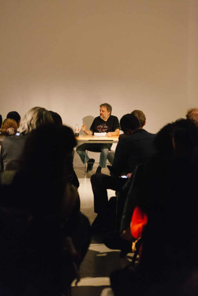 Zizek talking at a desk in front of an audience in the EDA pit.