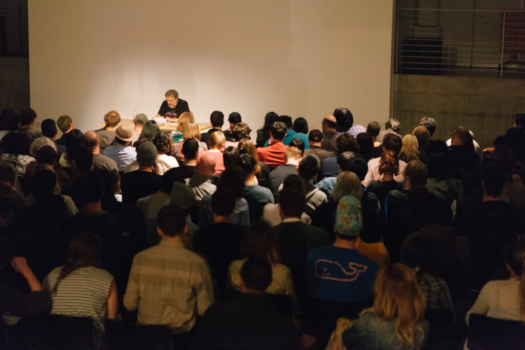 Zizek reading papers at a desk in front of an audience in the EDA pit.